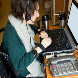 Image of woman working at computer using assistive devices