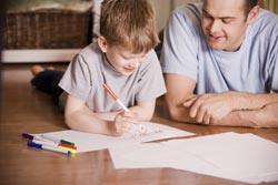 Image of father watching son draw with markers