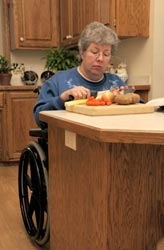 Image of woman in wheelchair preparing food at kitchen counter